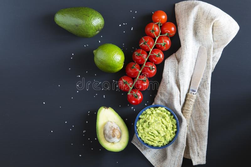 Traditional latinamerican mexican sauce guacamole in ceramic bowl and ingredients on dark background. Top view. Flat lay. Copy space royalty free stock images