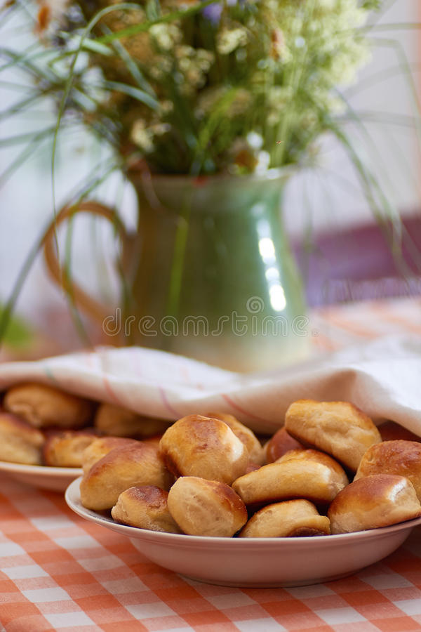 Traditional latvian bacon pies. And meadow herbs background. Rustic style royalty free stock image