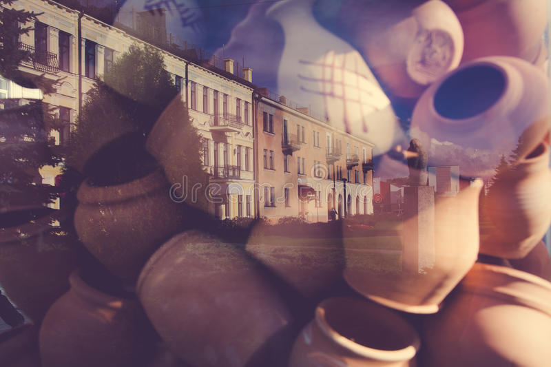 Traditional Latvian pots reflecting in a glass. On the buildings background. Double exposure effect royalty free stock images