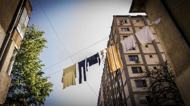A laundry stretched out on the street drying in the midday sun. Traditional laundry and prolongation in old Europe stock image