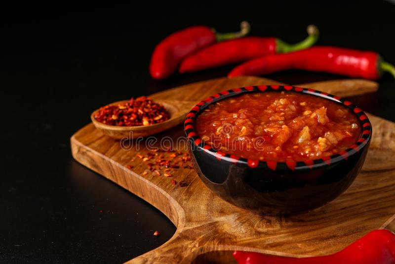 Traditional Maghrebi hot chili pepper sauce paste harissa on dark background, Tunisia and Arabic cuisine , horizontal orientation. Closeup stock images