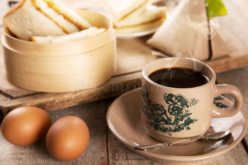 Traditional Malaysian Nanyang coffee and breakfast. Traditional kopitiam style Malaysian coffee and breakfast. Fractal on the cup is generic print. Soft focus stock photo
