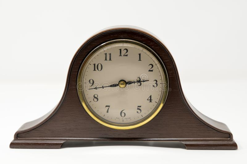 A traditional mantel clock with gold accents photographed against a white background stock photo
