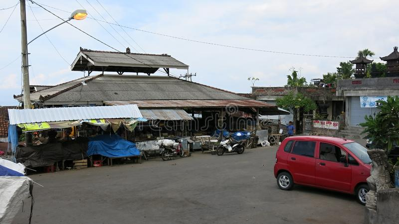 Traditional market building on Bali island in Indonesia. Stalls with sales goods. Parking for motorbikes, scooters and cars. Very. Simple equipment and design stock images