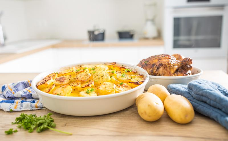 Traditional meal roasted potatoes and whole chicken on home kitchen table. Baked, food, dish, rustic, dinner, cooked, vegetable, background, delicious, herbs stock photography