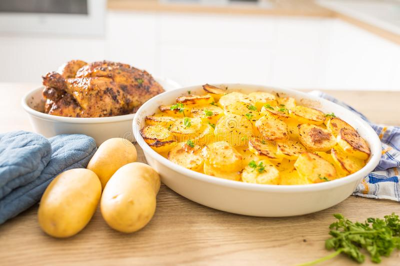 Traditional meal roasted potatoes and whole chicken on home kitchen table. Baked, food, dish, rustic, dinner, cooked, vegetable, background, delicious, herbs stock photos