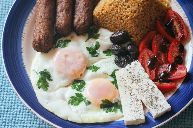 Traditional Mediterranean lunch. Bulgur, sausages, feta cheese, tomatoes with balsamic sauce, scrambled eggs with herbs, olives. stock photo