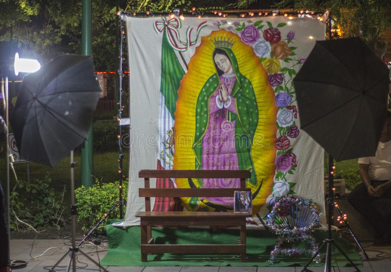 Traditional mexican day of the dead offering altar with a picture of the Virgin of Guadalupe, yellow flowers, bread and fruits in. Traditional mexican day of the stock image