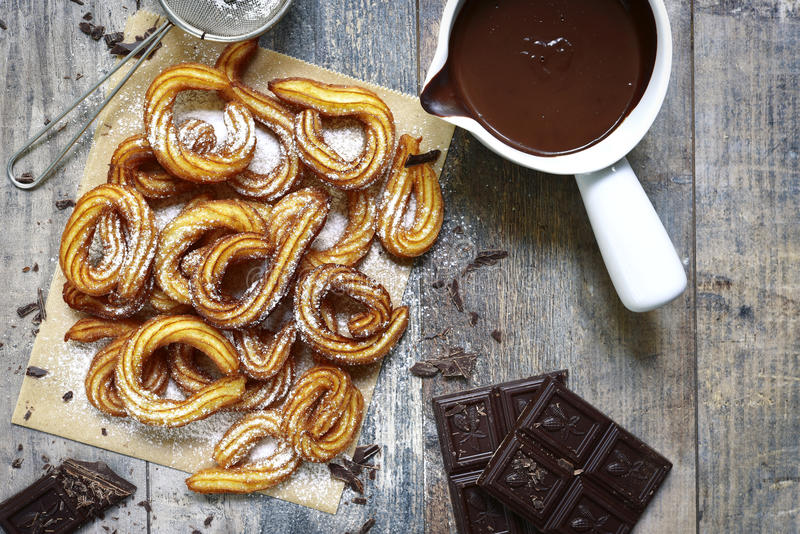 Traditional mexican dessert churros with chocolate sause. Traditional mexican dessert churros with chocolate sause on a rustic background stock photography