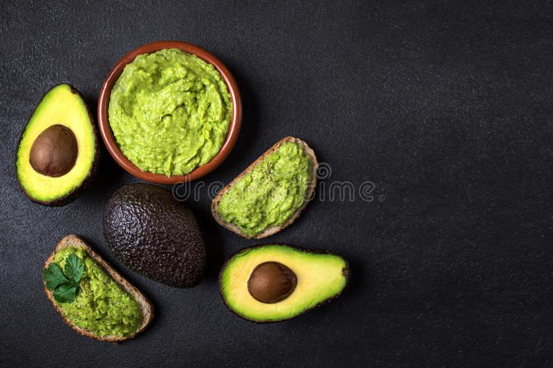 Traditional Mexican Dip Sauce Guacamole in a bowl with bread toasts, whole and cut half avocado on dark background. Top view. C. Opy space stock photo