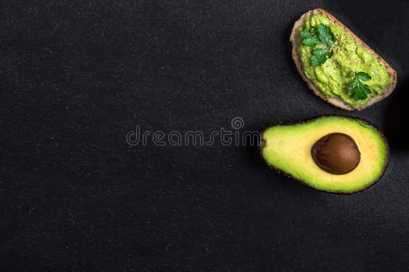 Traditional Mexican Dip Sauce Guacamole in a bowl with bread toasts,  whole and cut half avocado  on dark background. Top view. C. Traditional Mexican Dip Sauce stock images