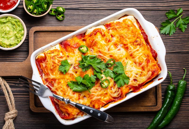 Traditional Mexican enchiladas. Traditional Mexican dish enchiladas with meat, chili red sauce and cheese in white casserole dish over rustic wooden background royalty free stock image
