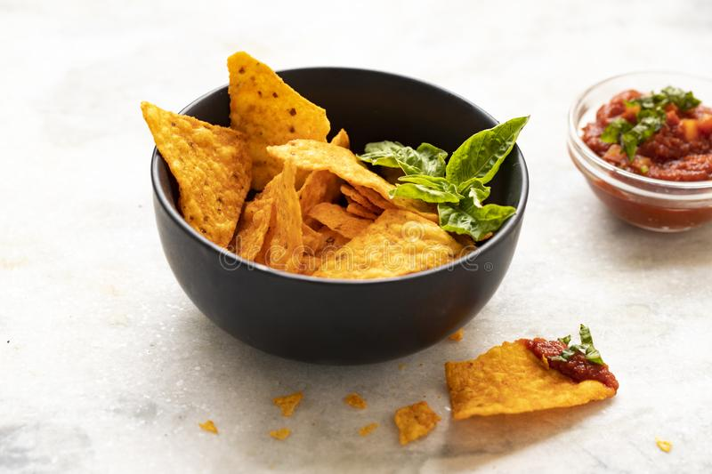 Bowlof corn chips nachos with guacamole on marble kitchen table. Nachos chips snack. Traditional mexican food closeup on white royalty free stock images