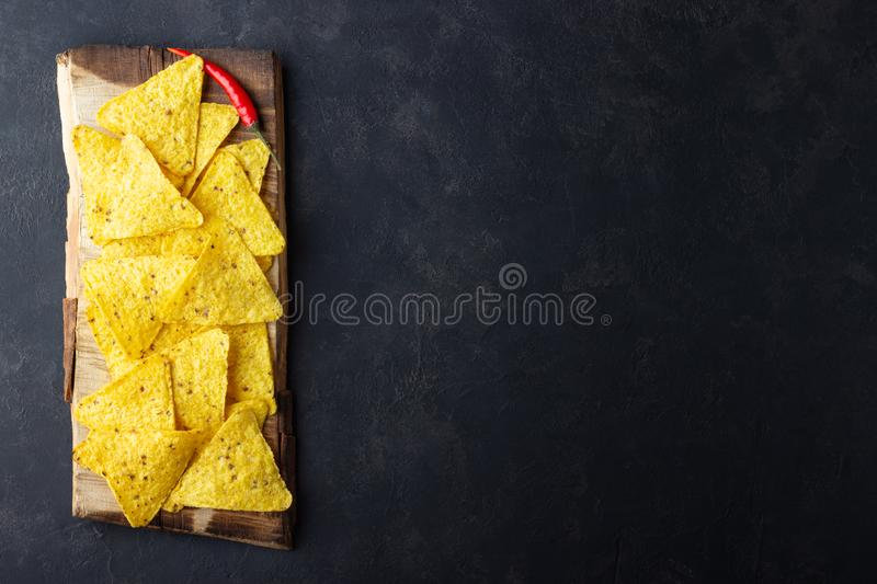Traditional Mexican food corn chips nachos on black background. Top view with copy space stock images