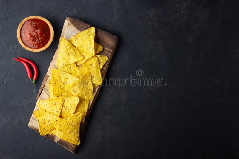 Traditional Mexican food corn chips nachos with salsa sauce on black background. Top view with copy space royalty free stock photography