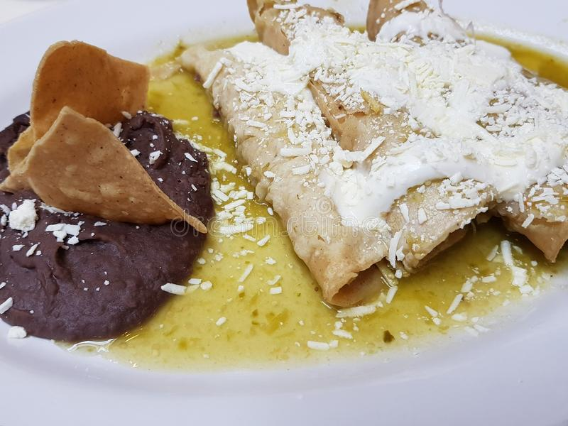 dish with green enchiladas and refried beans, typical mexican food royalty free stock photos