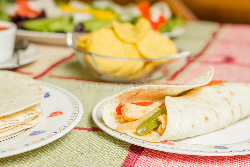 Traditional mexican food with a plate of chicken fajita, tortillas, fresh salad and a bowl of nachos royalty free stock photo