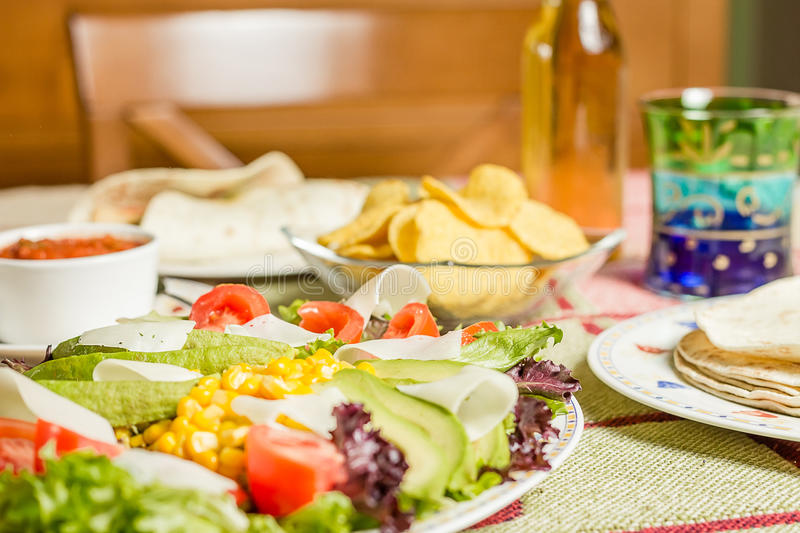 Traditional mexican food with a plate of fresh salad, tortillas, chicken fajitas, nachos and a bowl of spicy sauce royalty free stock photography