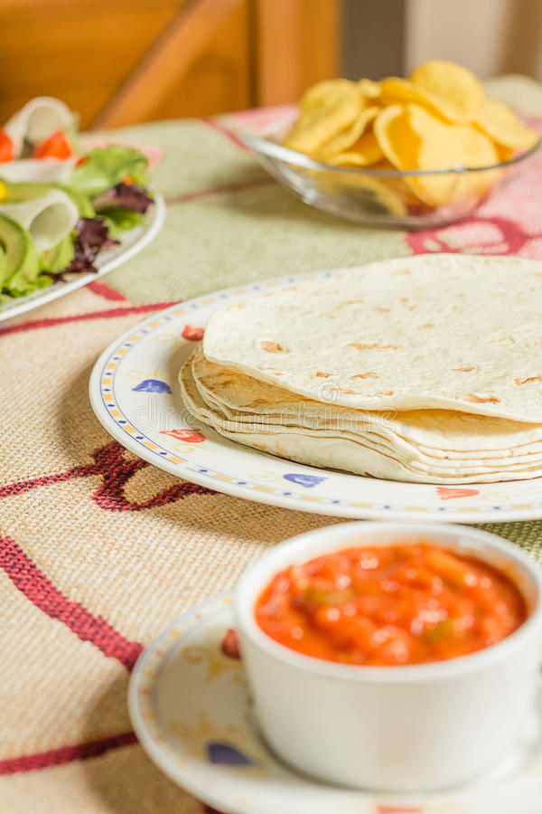Traditional mexican food with a plate of tortillas, fresh salad, nachos and a bowl of spicy sauce royalty free stock images