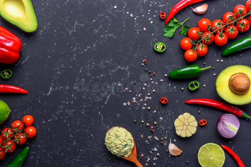 Traditional Mexican Guacamole sauce in spoon and ingredients on black stone table. Top view with copy space. Traditional Mexican Guacamole sauce in spun and stock images