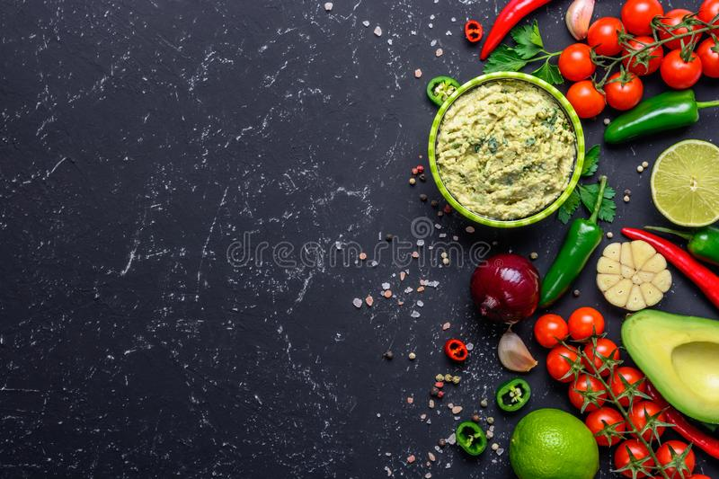 Traditional Mexican Latin American sauce Guacamole and ingredients on black stone table. Top view copy space stock photos
