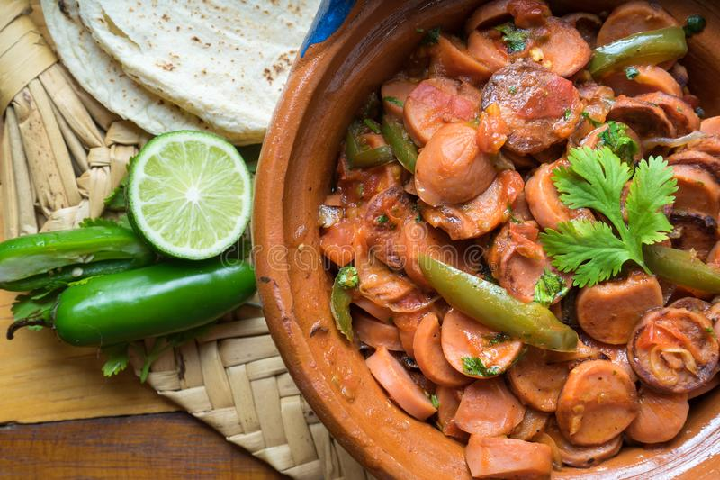 Mexican sausage stew with serrano pepper and tomato. Traditional mexican sausage stew with serrano pepper and tomato royalty free stock image