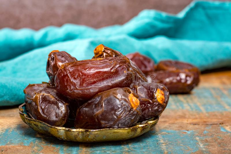 Traditional Middle East dessert, healthy food, big medjool dates. Fruits served on old blue wooden table royalty free stock image