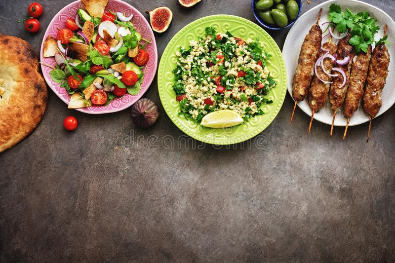 Traditional Middle Eastern and Arabian cuisine on a dark rustic background, border. Meze party food. Top view, flat lay, overhead, royalty free stock photo