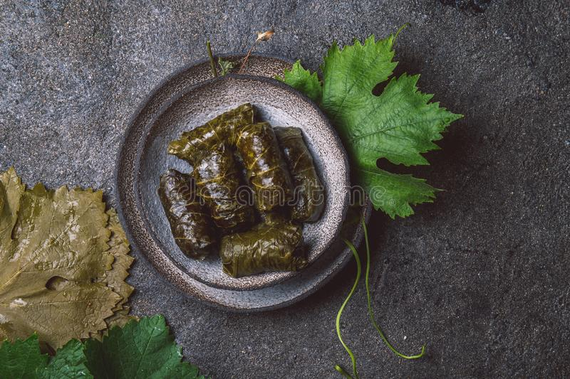 Traditional Middle Eastern dolma or tolma. Grape leaves stuffed with meat and rice. On Gray plate, gray concrete royalty free stock photography