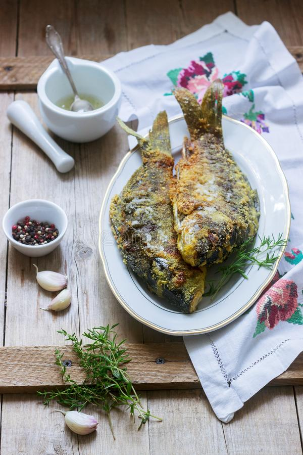Traditional Moldovan or Romanian dish, fried fish in corn breading served with garlic sauce. Rustic style. Traditional Moldovan or Romanian dish, fried fish in stock photography