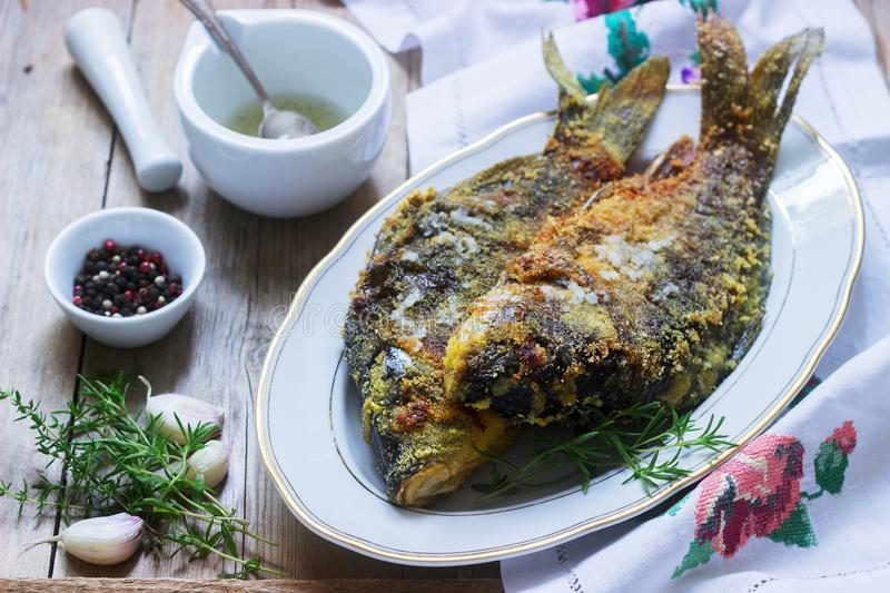 Traditional Moldovan or Romanian dish, fried fish in corn breading served with garlic sauce. Rustic style. stock photography