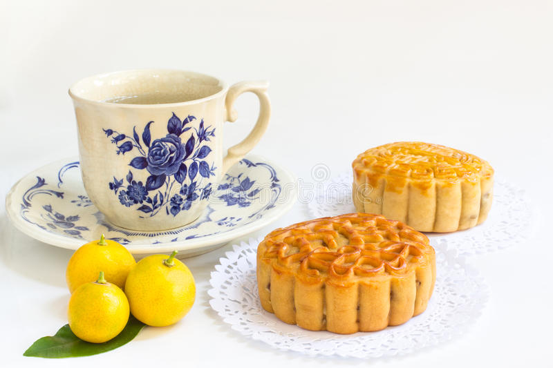 Traditional mooncake with teacup and small three oranges on leaves royalty free stock photography