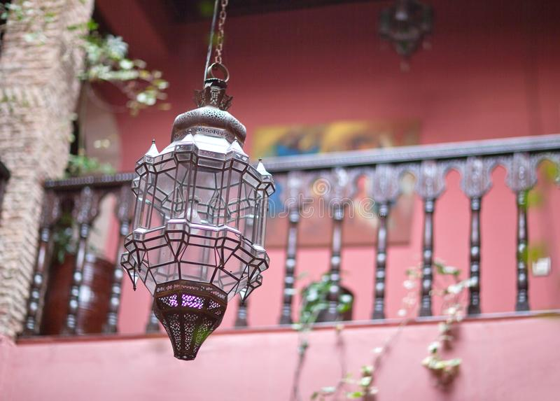 Traditional Moroccan glass copper lamp in oriental riad interior royalty free stock photography