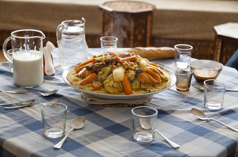 Family gathering around a couscous table concept. Morocco friday typical food. Traditional Moroccan homemade Couscous plate on a blue squared clothed table stock photos