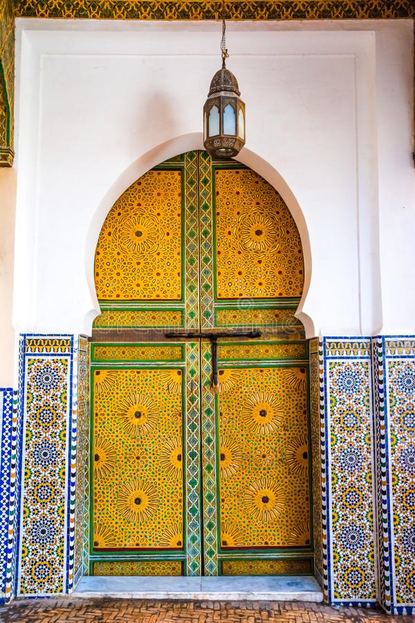 Traditional Moroccan style design of an ancient wooden entry door in the old Medina of Fez. Typical, old, intricately carved, royalty free stock photo