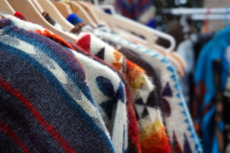 Traditional multi colored woolen knitwear clothes for sale on a market stall Traditional multi colored woolen knitwear clothes for. Sale on a market stall royalty free stock photo