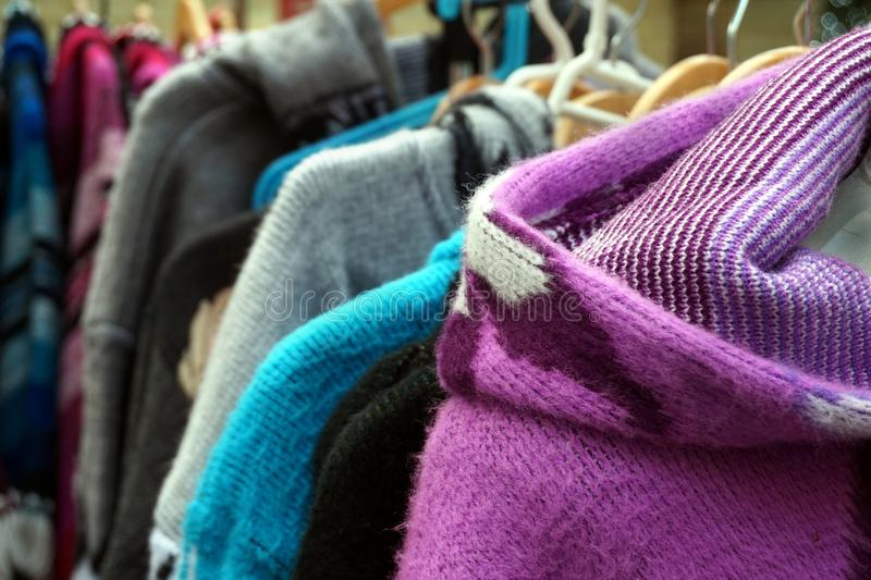 Traditional multi colored woolen knitwear clothes for sale on a market stall stock images