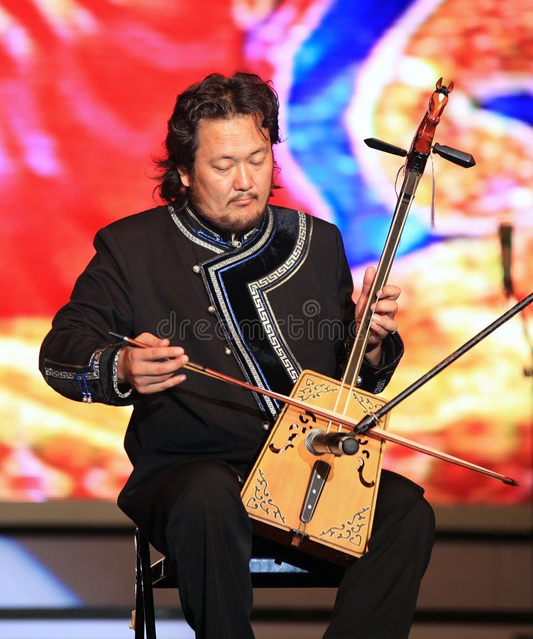 Traditional music of Mongolia. Shanghai - August 7: Artist performs on stage during Inner Mongolia Guangdian Arts Ensemble Concert at Shanghai World Expo 2010 on royalty free stock photos