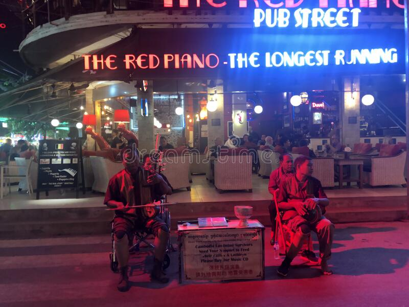 Traditional musical instrument performance in front of Red Piano Restaurant of Pub Street in Siem Reap, Cambodia stock photo