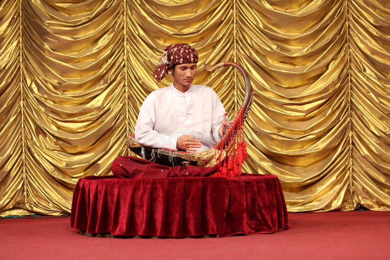Traditional musician in Myanmar. A traditional musician in Myanmar playing a saung harp royalty free stock photos