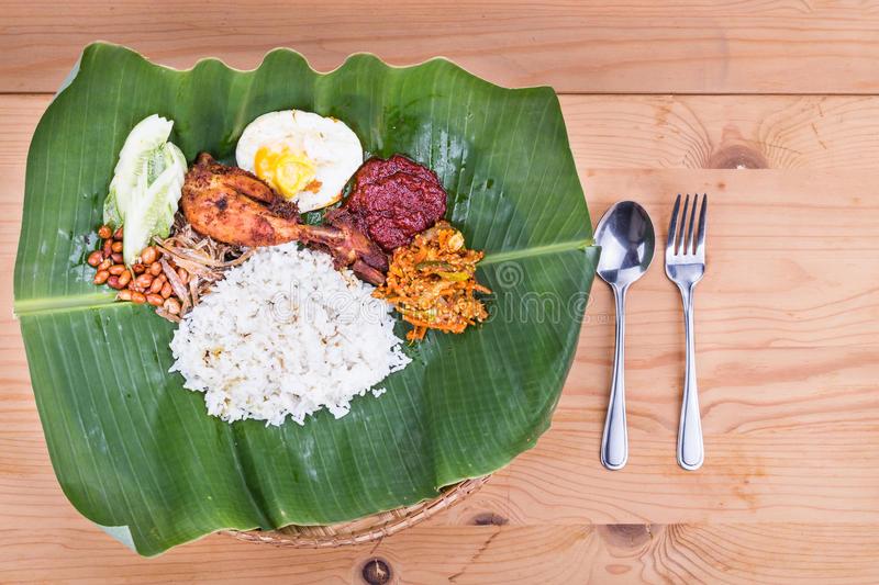 Traditional nasi lemak cuisine on banana leaf with fried chicken. Traditional nasi lemak meal on banana leaf with fried chicken, anchovies, groundnuts, fried royalty free stock photography