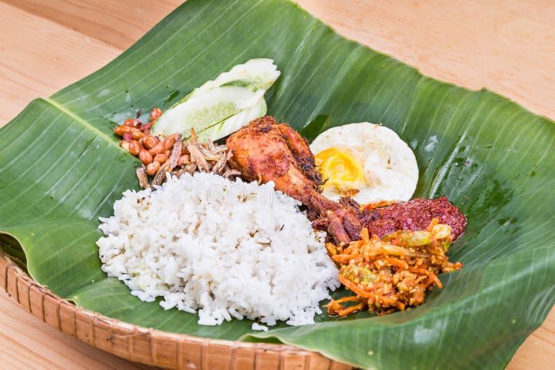 Traditional nasi lemak cuisine on banana leaf with fried chicken. Traditional nasi lemak meal on banana leaf with fried chicken, anchovies, groundnuts, fried stock images
