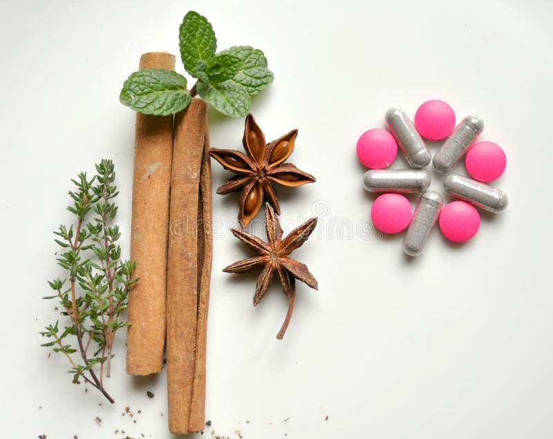 Traditional, natural remedy versus modern pills. Natural remedy versus modern medicine : various leaves with pills. Mint leaf, cinammon, thyme, anice star stock photos