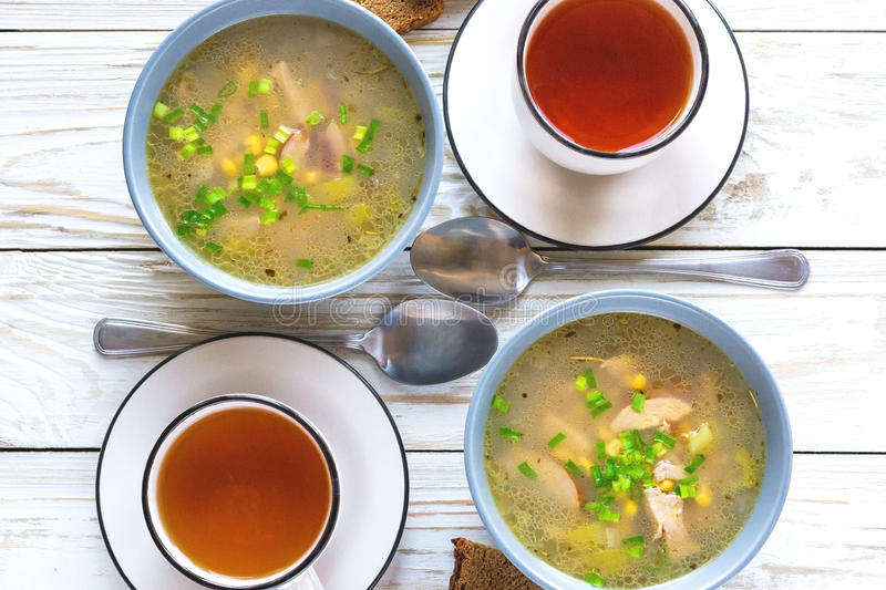 Traditional Nigerian corn and smoked chicken clear soup. And tea for breakfast at wooden table. Closeup royalty free stock photos