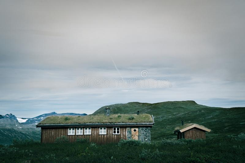 Traditional Norwegian huts in the mountain valley. Jotunheimen National Park mountains in the background. Huts roofs are covered with grass stock photos