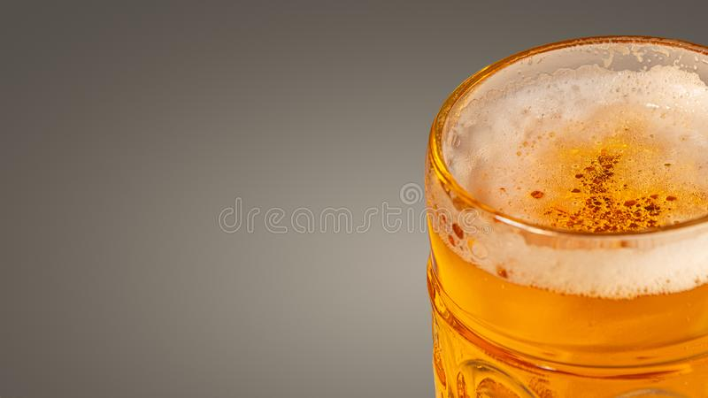 Traditional Octoberfest Bavarian beer in a big glass with wet walls at grey smooth gradient background. Banner, paste space royalty free stock photography