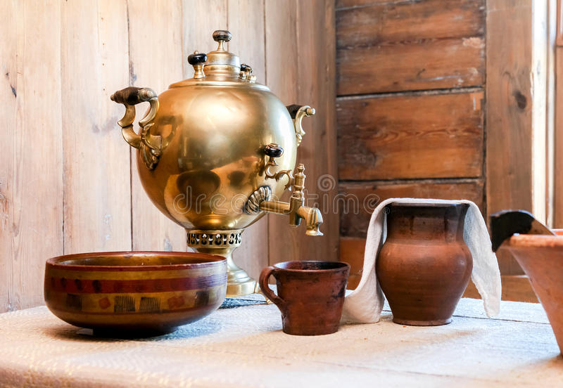 Traditional old copper samovar for tea drinking and ceramic ware royalty free stock images