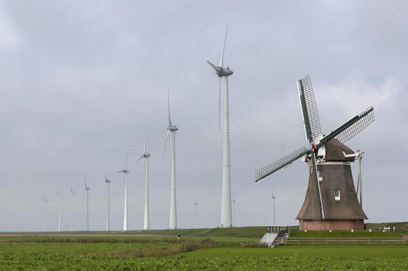 Traditional old dutch windmill goliath and wind turbines near eemshaven in the northern province groningen of the netherlands. And blue sky stock photos