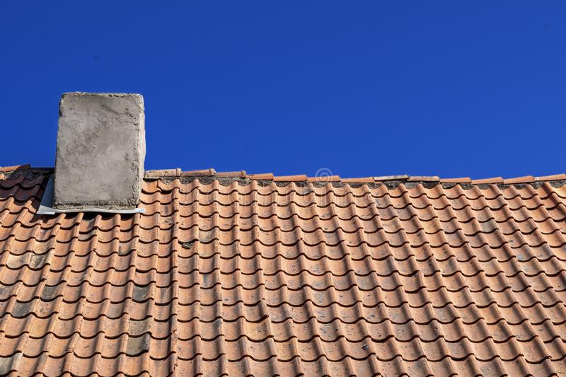 Traditional old Tile Roofing made of clay. Natural roofing material. Clay tiles with chimney on the background of blue sky. Traditional old Tile Roofing made of stock photos