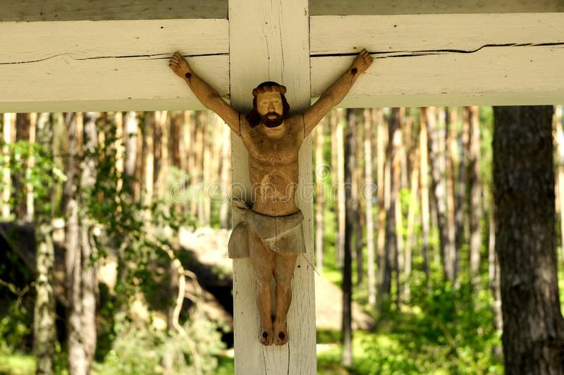 Traditional old wooden crucifix with Jesus christ painted sculpture from national folk culture park nearby Riga city, Latvia. Religious background royalty free stock image